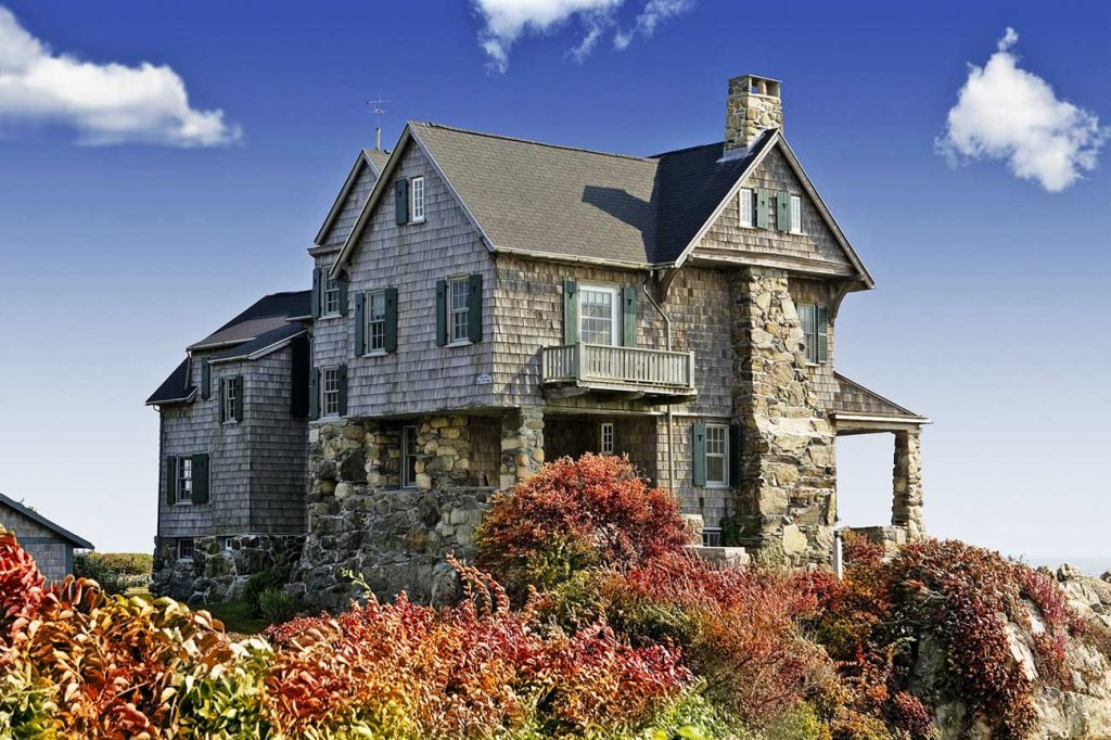 2 story house with stone exterior. Blue sky with clouds. Bushes.