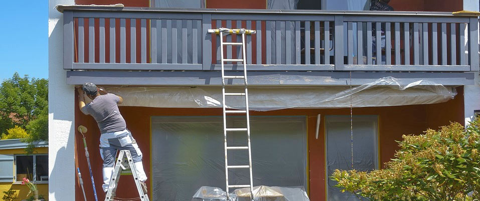 Painter on a ladder in front of a 2 story house. Railing. Lean-to ladder.