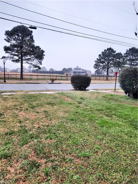 View from lot at 614 Washington Avenue, Cape Charles, Virginia 23310 with view of street and property across the street, bushes, trees, a house in the distance, fence.