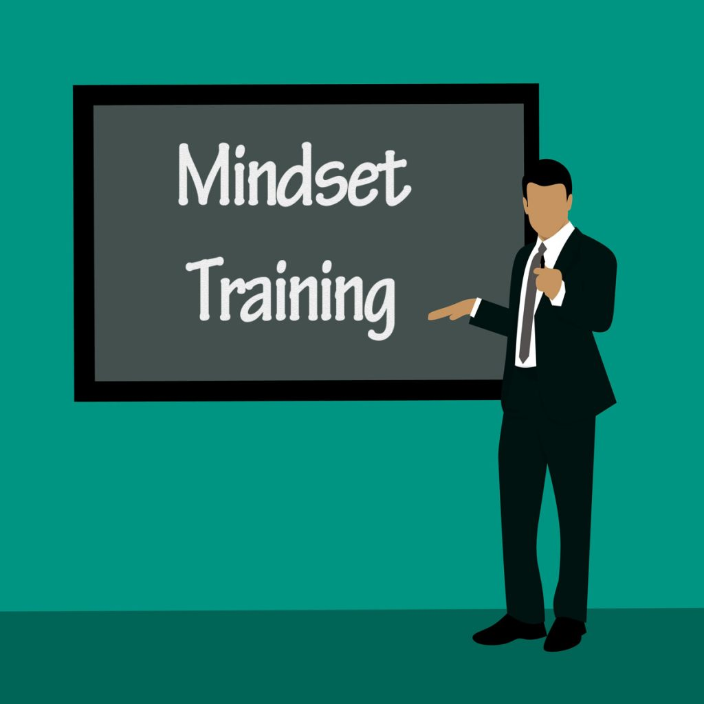 Man, Chalkboard with Mindset training written in chalk.